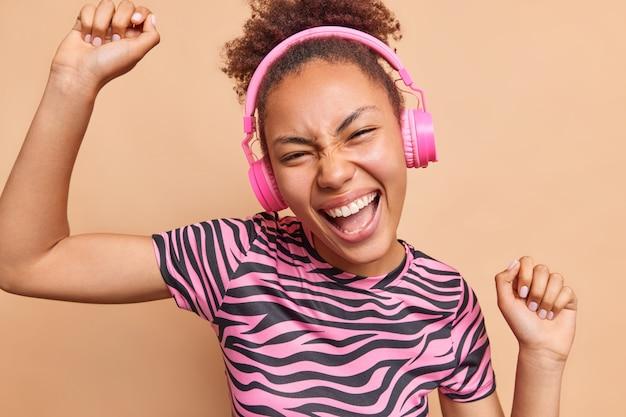 腕を上げて笑顔で踊る楽しいミレニアル世代の女性は、プレイリストからのお気に入りの音楽を広く楽しんでいますベージュの壁に隔離されたカジュアルな服を着たワイヤレスヘッドフォンを着用しています
