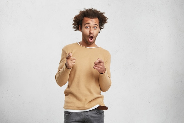 Joyful mixed race man wears sweater, points finger at camera, chooses you, opens mouth widely