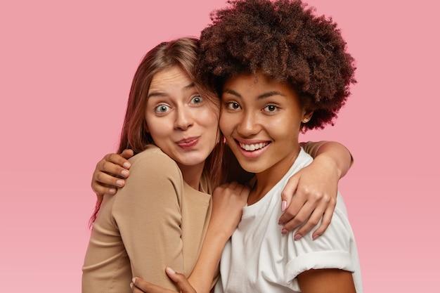 Радостные женщины смешанной расы обнимаются и смотрят с довольным выражением лица, поддерживают дружеские отношения.