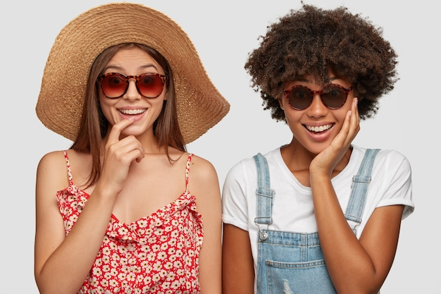 Joyful mixed race women wear shades