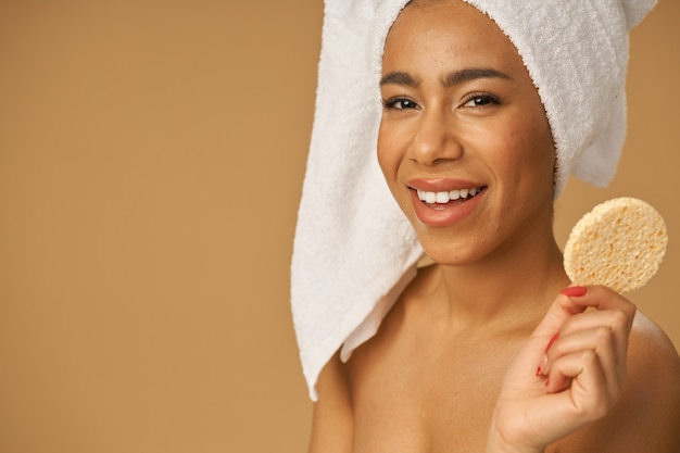 Joyful mixed race young woman holding cleansing face sponge, posing isolated over beige background