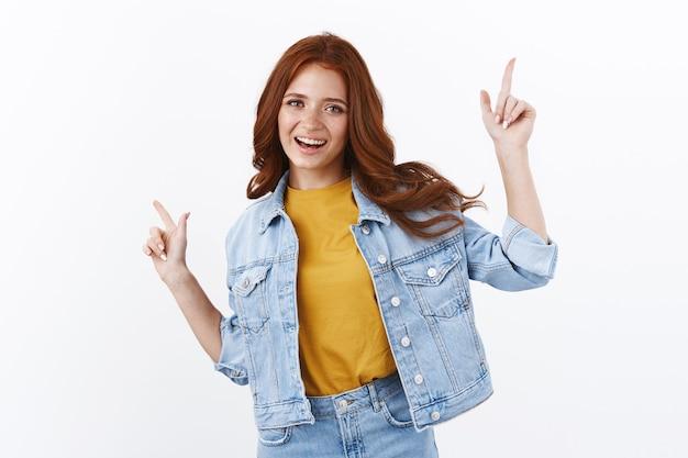 Радостная современная нахальная рыжая девушка с веснушками в джинсовой куртке, радостно танцует, делает покупки по ссылкам на онлайн-шоу, показывает вверх влево и вправо, беззаботно улыбается, развлекается стоящей белой стеной