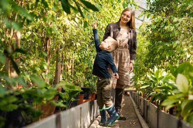 즐거운 엄마와 아들이 온실에서 걷고 있다