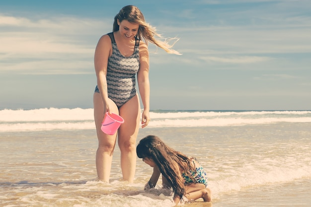 Joyful mom and little daughter standing ankle deep in sea water and wet sand, picking shells into bucket