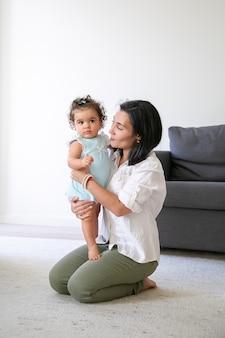 집에서 바닥에 앉아, 달콤한 아기 딸 팔에 들고 즐거운 엄마. 세로 샷. 부모와 어린 시절 개념