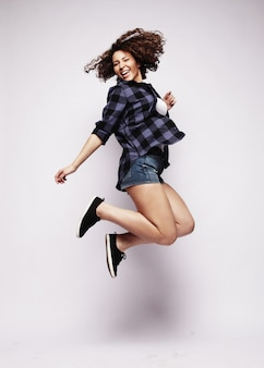 うれしそうな瞬間。ジャンプしてホワイトスペースに笑みを浮かべてショートパンツを着ている美しいe少女の完全な長さの肖像画