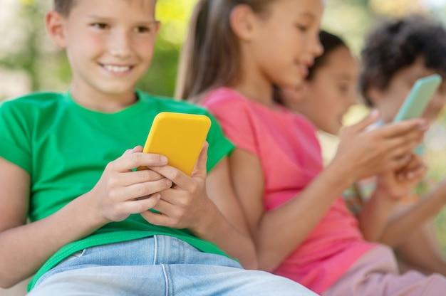 즐거운 순간들. 노란색 스마트폰과 여름날 야외에 앉아 있는 친구들과 함께 녹색 티셔츠를 입은 웃고 있는 즐거운 소년