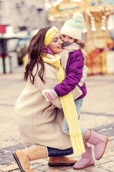 즐거운 분위기. 세미 위치에 서서 그녀의 딸 가까이에 서있는 놀라운 젊은 여성