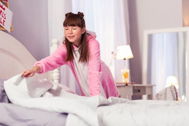 Радостное настроение. привлекательный длинноволосый ребенок с улыбкой на лице, глядя на одеяло