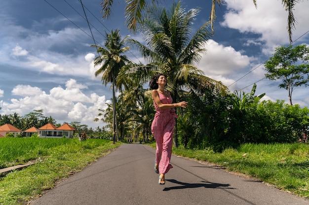 즐거운 분위기. 그녀의 걷는 동안 높이 점프하는 동안 그녀의 얼굴에 미소를 유지하는 쾌활한 여자