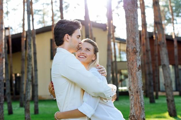 うれしそうな気分。彼女の最愛の夫と一緒に立っている間笑顔で喜んでポジティブな女性