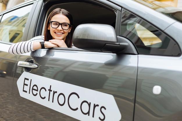 즐거운 분위기. 그녀의 새로운 전기 자동차에 앉아 즐거운 아름 다운 여자
