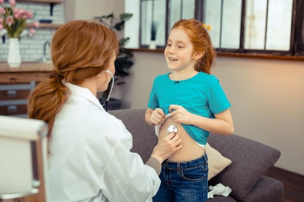 즐거운 분위기. 의사에게 그녀의 배꼽을 보여주는 동안 웃 고 긍정적 인 귀여운 소녀