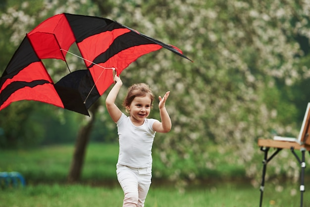 Joyful mood. positive female child running with red and black colored kite in hands outdoors