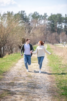 うれしそうな気分。晴れた晴れた日に手をつないで自然の中を走るカジュアルな服を着た若い大人の楽しい男女