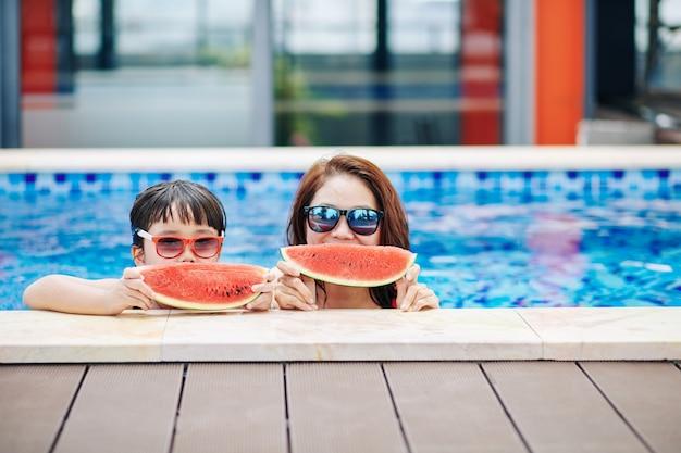 즐거운 어머니와 선글라스에 작은 딸이 수영장에 서서 신선한 수박을 먹고