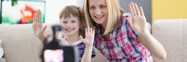 Joyful mother and daughter hold their hand in greeting to video camera screen