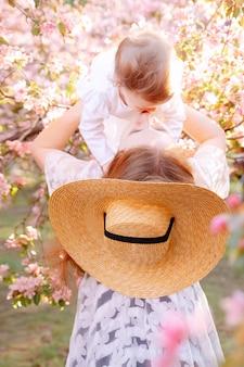 즐거운 어머니는 귀여운 어린 소녀와 행복한 가족 시간을 즐기고 어머니의 날에 그녀를 들어올립니다.