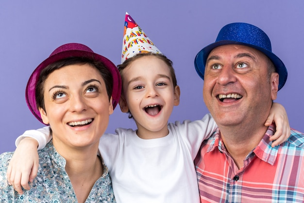Joyful mother and father with party hats looking up standing with their son isolated on purple wall with copy space