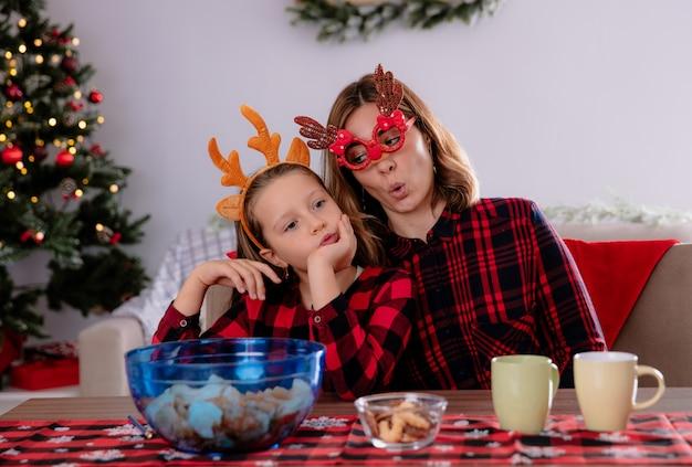 Madre allegra che gioca con la figlia seduta a tavola godendo il periodo natalizio a casa