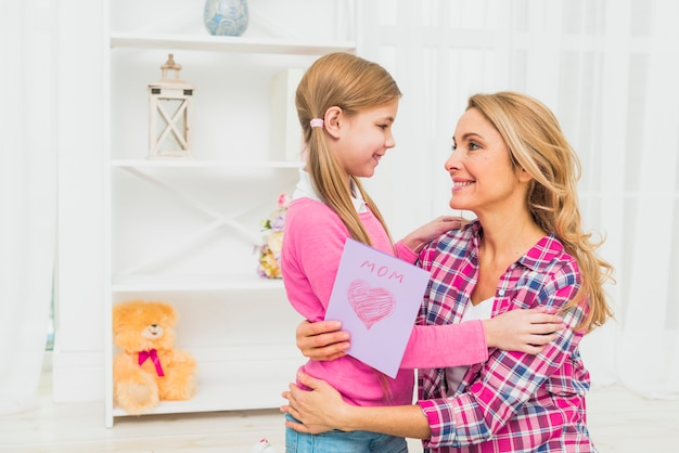 Joyful mother with greeting card hugging daughter