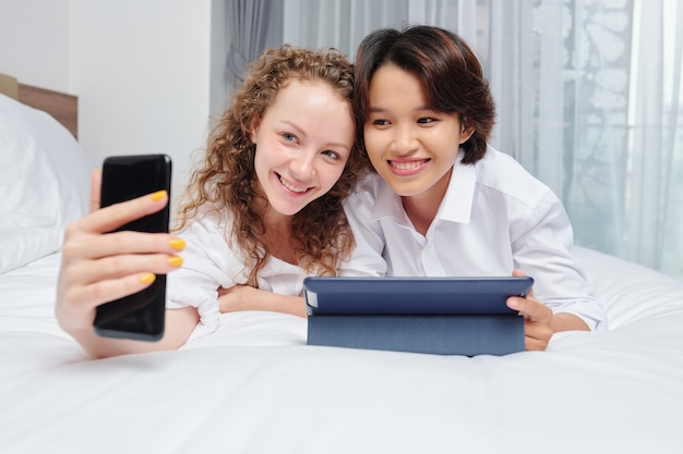 Радостные многоэтнические подруги лежат на кровати с планшетным компьютером и делают селфи на смартфоне