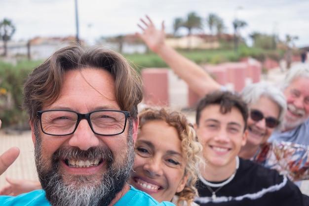 즐거운 다세대 가족이 함께 재미, 부모, 십대 아들 및 조부모. 카메라를보고 행복하게 웃고