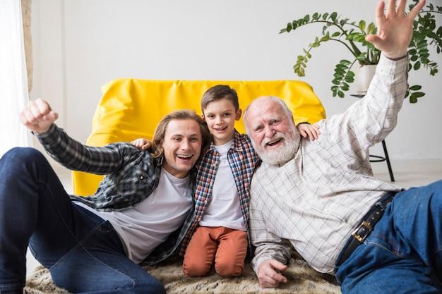 一緒にカーペットの上に座ってうれしそうな多世代家族