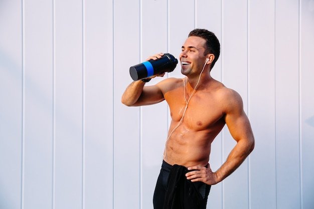 Joyful muscular guy enjoying drinking a water after workout, listening to music in earphones