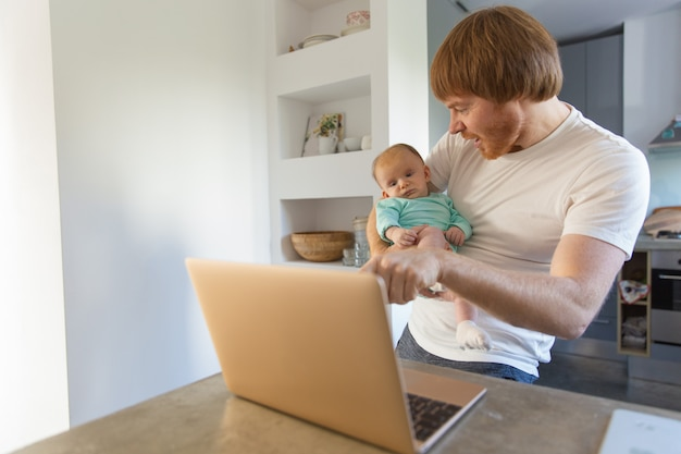 Joyful new dad and his baby daughter watching content