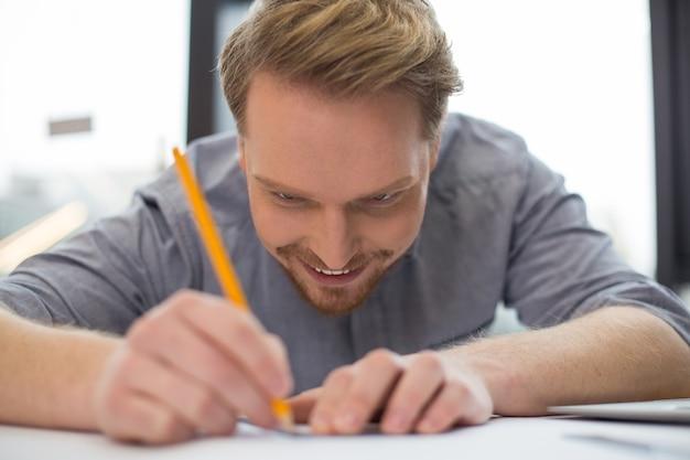 테이블에 앉아 작업에 집중하면서 그림을 그리는 즐거운 좋은 기뻐하는 남자