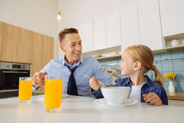 Радостный милый довольный мужчина сидит вместе со своей дочерью и смотрит на нее