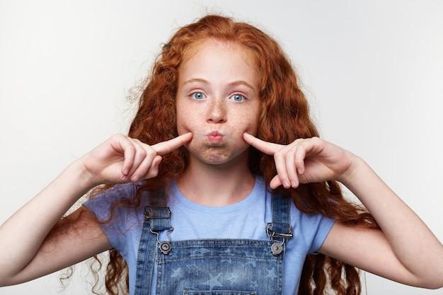 生姜の髪とそばかすのあるうれしそうな素敵な女の子は、カメラを見て、頬と唇を吹いて、指で頬に触れて、面白く見え、白い背景の上に立っています。