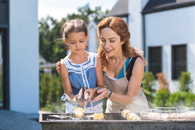 Joyful nice mother and daughter standing together while grilling corn