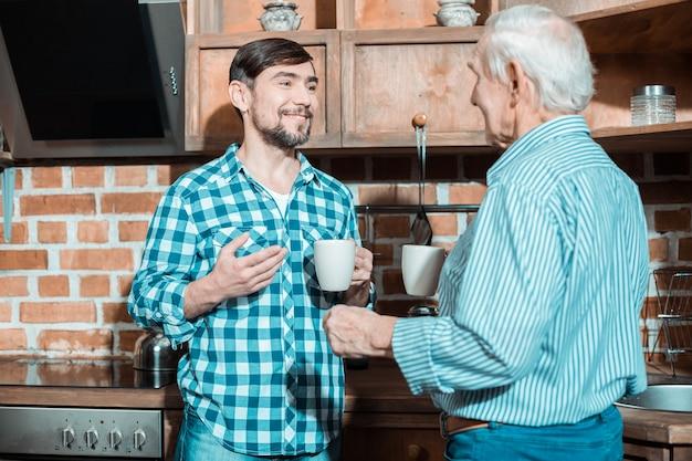 うれしそうな素敵なポジティブな父と息子が一緒にお茶を飲み、お互いの会社を楽しみながら話している