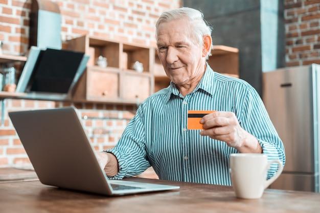 彼のクレジットカードを使用しながら笑顔でノートパソコンの画面を見ているうれしそうな素敵な年配の男性