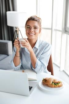 リビングルームのテーブルに座ってコーヒーを飲み、ラップトップを使用して眼鏡をかけてうれしそうな素敵な女性