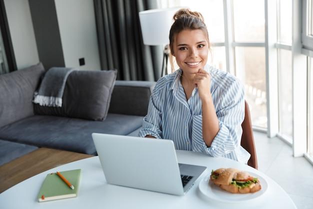 リビングルームのテーブルに座っている間笑顔でラップトップを使用してうれしそうな素敵な女性