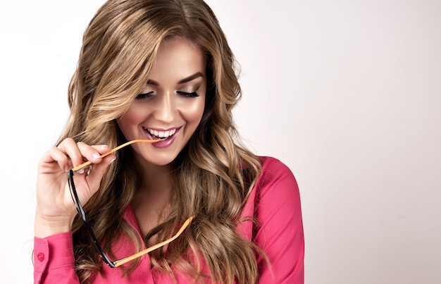 얼굴에 이빨 미소와 손에 안경을 가진 즐거운 멋진 젊은 금발 머리 여자