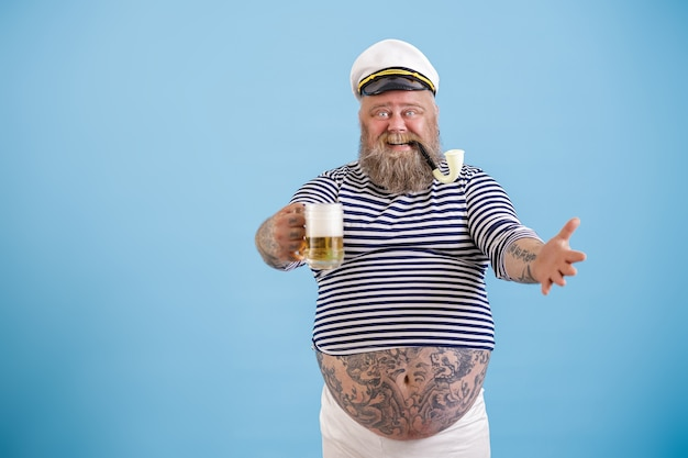 喫煙パイプとうれしそうな肥満の船乗りは、水色の背景に新鮮なビールのガラスを保持します。