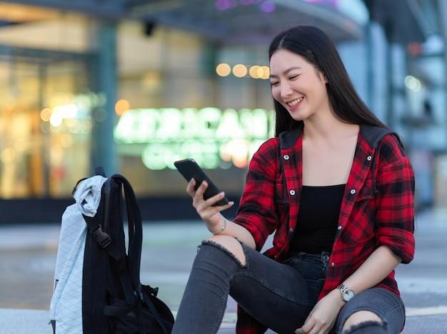 Радостная азиатская молодая женщина-путешественница смотрит смешное видео по телефону в чате с друзьями