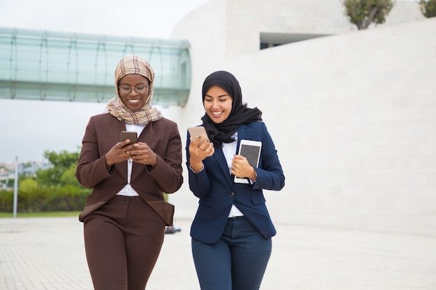 Joyful office female friends with smartphones chatting outside
