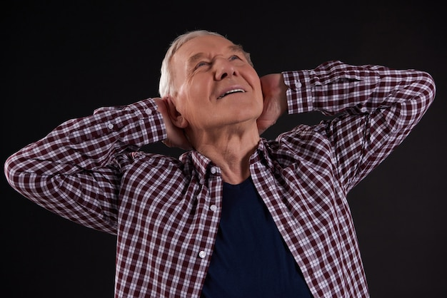 Joyful old man looks up with hands on back of neck