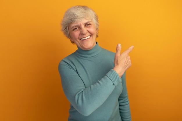 복사 공간이 있는 주황색 벽에 격리된 쪽을 가리키는 파란색 터틀넥 스웨터를 입은 즐거운 노부인