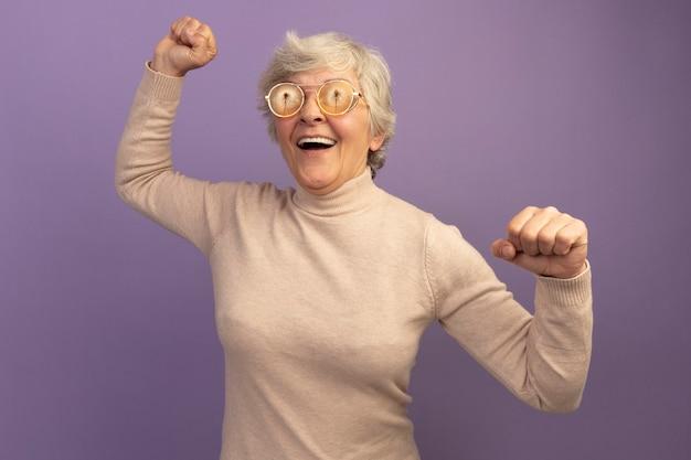 クリーミーなタートルネックのセーターとメガネを身に着けているうれしそうな老婆は、紫色の壁に隔離された拳を上げる側を見て