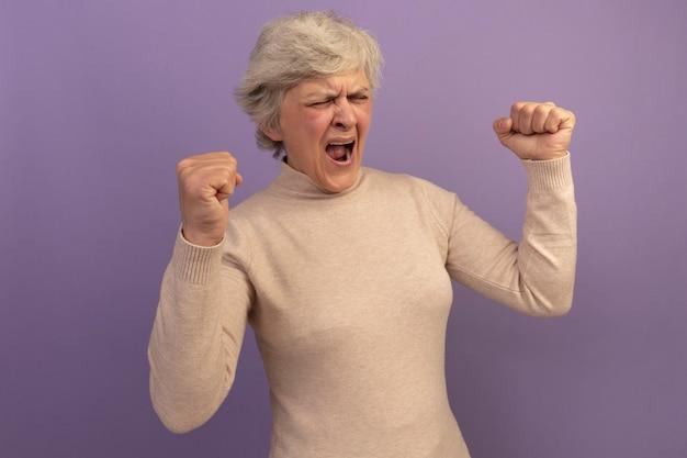 Una donna anziana allegra che indossa un maglione a collo alto cremoso che fa un gesto di sì con gli occhi chiusi isolati su un muro viola