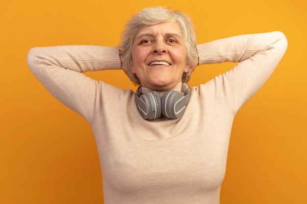 Joyful old woman wearing creamy turtleneck sweater and headphones around neck putting hands behind head isolated on orange wall
