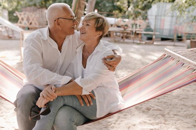 블라우스와 격자 무늬 해먹에 앉아 청바지에 금발의 멋진 헤어 스타일을 가진 즐거운 늙은 여자와 해변에서 회색 머리 남자를 웃고 포옹.