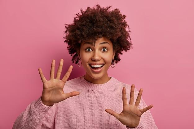 즐거운 낙관적 인 어두운 피부의 젊은 여성이 손을 들고 친근한 인사 제스처를하고 인사하거나 인사하고 넓은 미소로 누군가를 환영하며 곱슬 머리를 가졌으며 분홍색 벽에 포즈를 취합니다.