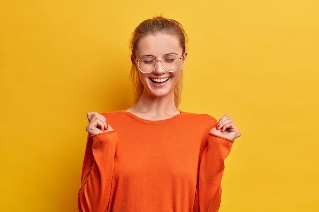 Gioiosa ragazza ottimista con un sorriso felice, chiude gli occhi, alza le mani, ridacchia per qualcosa di positivo, indossa occhiali da vista e maglione arancione,